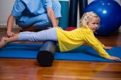 Fysioterapeut som ger sjukgymnastik till flickan royaltyfria bilder