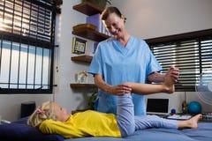 Fysioterapeut som ger sjukgymnastik till flickan royaltyfri foto