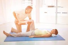 Fysioterapeut som ger sjukgymnastik till gravida kvinnan Arkivbilder