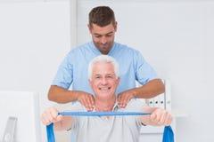Fysioterapeut som hjälper den höga patienten, i att öva med motståndsmusikbandet royaltyfri fotografi