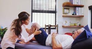 Fysioterapeut som mäter det tålmodiga knäet med den medicinska linjalen 4k lager videofilmer