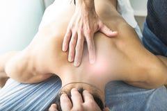 Fysioterapeut som masserar baksidan och halsen av en ung man Begrepp av wellnessen och sjukgymnastik arkivfoton