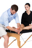 Fysioterapeut som masserar patienten Arkivbild