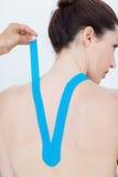 Fysioterapeut som tillbaka applicerar det blåa kinesiobandet till patienter Royaltyfria Foton