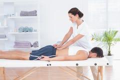 Fysioterapeut som tillbaka gör massage royaltyfri bild