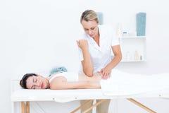 Fysioterapeut som tillbaka gör massage royaltyfri foto