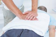 Fysioterapeut som tillbaka gör massage royaltyfri fotografi