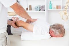 Fysioterapeut som tillbaka gör massage till hans patient arkivfoto
