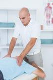 Fysioterapeut som tillbaka gör massage till hans patient royaltyfria foton