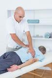 Fysioterapeut som tillbaka gör massage till hans patient fotografering för bildbyråer