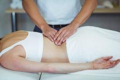 Fysioterapeut som tillbaka ger massage till en kvinna royaltyfri bild