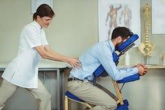 Fysioterapeut som tillbaka ger massage till en patient arkivfoto