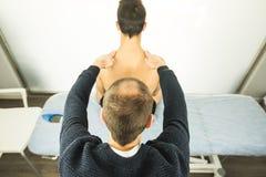 Fysioterapeut som tillbaka undersöker en ung man Sjukgymnastikbegrepp royaltyfria bilder
