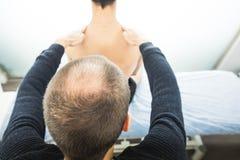 Fysioterapeut som tillbaka undersöker en ung man Sjukgymnastikbegrepp arkivfoton