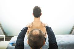 Fysioterapeut som tillbaka undersöker en ung man Sjukgymnastikbegrepp royaltyfri bild