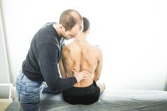 Fysioterapeut som tillbaka undersöker en ung man Sjukgymnastikbegrepp royaltyfri foto