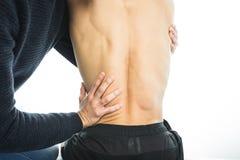 Fysioterapeut som tillbaka undersöker en ung man Sjukgymnastikbegrepp royaltyfri fotografi