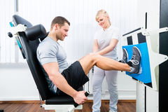 Fysioterapeut som övar patienten i sportterapi Arkivfoto