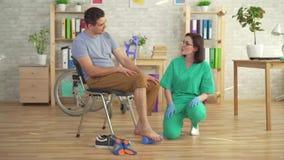 Fysioterapeuten hjälper en man i en rullstol med ortopediska problem att göra övningar för att korrigera plan fot med ett gummi stock video