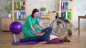 Fysioterapeuten i rehabiliteringmitten hjälper, i att värma benen av en tonårs- flicka i rehabilitering upp efter a arkivfilmer