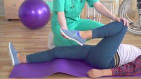 Fysioterapeuten i rehabiliteringmitten hjälper, i att värma benen av en tonårs- flicka i rehabilitering upp efter a stock video