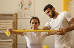 Fysioterapeuter som öva med motståndsmusikbandet Royaltyfri Fotografi