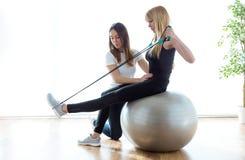 Fysioterapeutportionpatient som gör övning på konditionboll i physio rum royaltyfri bild