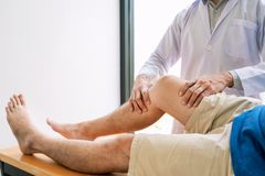 Fysiotherapeut artsenrehabilitatie het raadplegen fysiotherapie die uitoefenend beenbehandeling met pati?nt in fysiokliniek of ho royalty-vrije stock fotografie