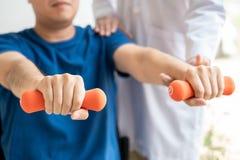 fysiotherapeut artsenrehabilitatie het raadplegen fysiotherapie die uitoefenend behandeling met pati?nt in fysiokliniek geven of stock afbeeldingen