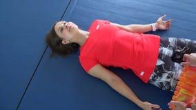 Fysiotherapeut die aan de vloer werken De vrouw doet een uitbreiding van de afdeling in de gymnastiek stock videobeelden