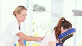 Fysiotherapeut die achtermassage doen aan haar patiënt