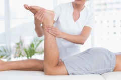 Fysiotherapeut die beenmassage doen aan haar patiënt Stock Afbeeldingen