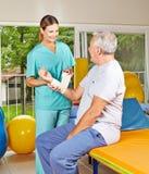 Fysiotherapeut die de hogere mens helpen Stock Fotografie