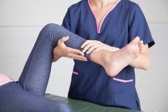 Fysiotherapeut die een beenbehandeling geven Stock Foto