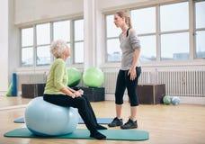 Fysiotherapeut die een hogere vrouw instrueren bij rehab Stock Foto's