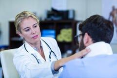 Fysiotherapeut die hals van patiënt onderzoeken stock afbeeldingen