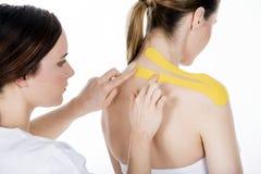 Fysiotherapeut die het vastbinden op de trapeziusvrouw krijgen Royalty-vrije Stock Foto's