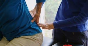 Fysiotherapeut die hogere vrouw terug in kliniek 4k onderzoeken stock videobeelden