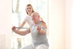 Fysiotherapeut die met bejaarde patiënt in kliniek werken stock foto
