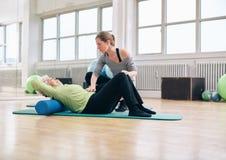 Fysiotherapeut die oudere vrouw helpen bij gymnastiek Stock Afbeelding