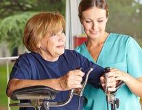 Fysiotherapeut die oudste helpen royalty-vrije stock afbeelding