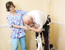 Fysiotherapeut die Patiënt helpt Stock Afbeeldingen