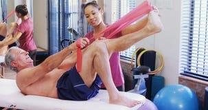 Fysiotherapeut die patiënt in het uitvoeren van oefening met weerstandsband 4k helpen stock footage