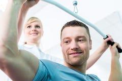 Fysiotherapeut die sportrehabilitatie met patiënt doen Stock Foto's