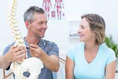 Fysiotherapeut die stekelmodel tonen aan zijn patiënt stock foto