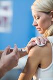 Fysiotherapeut die vrouwelijke patiënt inspuiten Stock Afbeeldingen