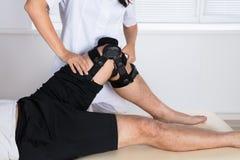 Fysiotherapeut Fixing Knee Braces op Mensen` s Been royalty-vrije stock afbeeldingen