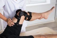Fysiotherapeut Fixing Knee Braces op Mensen` s Been stock fotografie