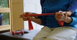 Fysiotherapeut het verbeteren positie van hogere vrouw in kliniek 4k stock video