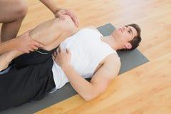 Fysiotherapeut jong onderzoeken bemant been Stock Foto